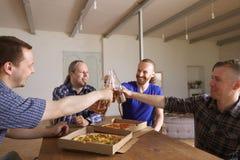 Cerveza del tintineo de los amigos sobre la pizza foto de archivo libre de regalías