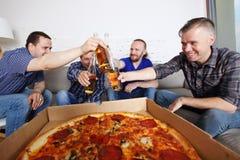 Cerveza del tintineo de los amigos sobre la pizza imagenes de archivo