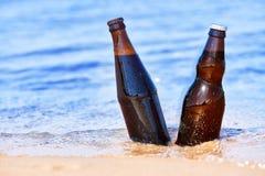 Cerveza en agua en la costa Imagen de archivo
