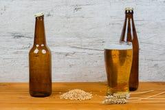 Cerveza en botellas y vidrio con los oídos de la cebada fotos de archivo libres de regalías