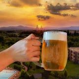 Cerveza en la puesta del sol Imagen de archivo libre de regalías