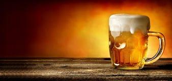 Cerveza en la tabla de la madera imagen de archivo libre de regalías