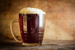 Cerveza en taza en fondo de madera rústico Foto de archivo libre de regalías