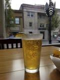 Cerveza en una tabla con una opinión de la ventana imagen de archivo