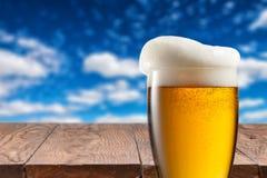 Cerveza en vidrio en la tabla de madera contra el cielo azul Imagenes de archivo
