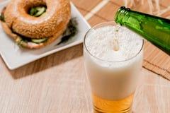 Cerveza en vidrio y hamburguesa en la tabla de madera Fotografía de archivo libre de regalías