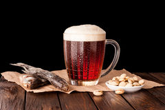 cerveza fría oscura en una taza escarchada en la tabla de madera oscura Imagenes de archivo