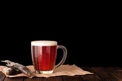 cerveza fría oscura en una taza escarchada en la tabla de madera oscura Fotografía de archivo