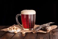cerveza fría oscura en una taza escarchada en la tabla de madera oscura Fotografía de archivo libre de regalías