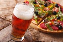 Cerveza fría y pizza caliente en el primer de la tabla horizontal Imagen de archivo