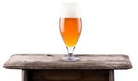 Cerveza fresca escarchada con la espuma aislada en la tabla de madera Fotografía de archivo