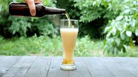 Cerveza ligera de colada del proceso en el vidrio alto de la botella de vidrio oscuro en jardín del verano en la tabla de madera almacen de metraje de vídeo