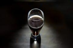 Cerveza oscura artística en fondo negro Foto de archivo