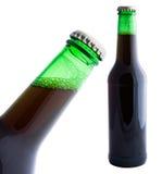 Cerveza oscura en la botella verde aislada en el fondo blanco Imagen de archivo