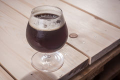 Cerveza oscura en la tabla de madera foto de archivo libre de regalías
