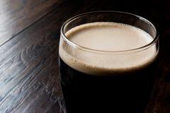 Cerveza oscura en superficie de madera Foto de archivo libre de regalías