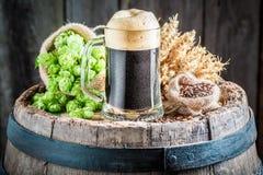 Cerveza oscura fresca con espuma, los saltos y el trigo grandes Fotografía de archivo