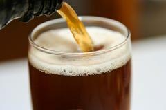 Cerveza oscura que vierte en un vidrio Fotografía de archivo