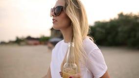 Cerveza que camina y de consumición de la mujer bonita joven de la botella de cristal en la playa durante puesta del sol, tiro de almacen de metraje de vídeo