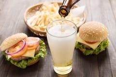Cerveza que es vertida en el vidrio con las hamburguesas y el francés gastrónomos Foto de archivo