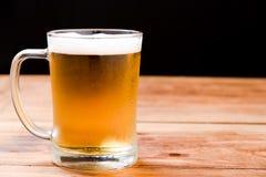 Cerveza que vierte del top en botella en la tabla de madera Foto de archivo