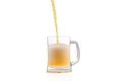Cerveza que vierte en el vidrio semilleno sobre el fondo blanco Fotografía de archivo