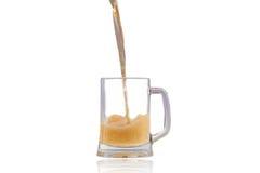 Cerveza que vierte en el vidrio semilleno sobre el fondo blanco Fotos de archivo libres de regalías