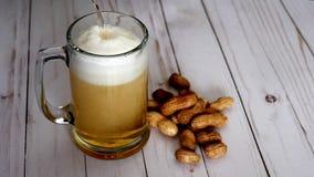 Cerveza que vierte en la taza y los cacahuetes metrajes