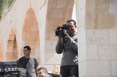 Cerveza-Sheva, ISRAEL - 5 de marzo de 2015: Cameraman en el trabajo Funcionamiento del tiroteo contra la perspectiva del edificio Foto de archivo libre de regalías