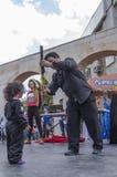 Cerveza-Sheva, ISRAEL - 5 de marzo de 2015: El ayudante y el niño del mago en la escena de la calle - Purim Fotografía de archivo