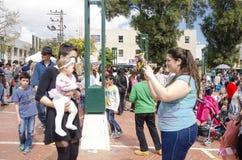 Cerveza-Sheva, ISRAEL - 5 de marzo de 2015: La muchacha llena fotografió a la novia con un bebé en sus brazos en la calle Purim Imagenes de archivo