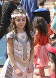 Cerveza-Sheva, ISRAEL - 5 de marzo de 2015: Muchacha en un vestido con una guirnalda blanca de flores artificiales en el pelo lar Imagen de archivo