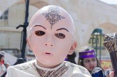 Cerveza-Sheva, ISRAEL - 5 de marzo de 2015: Muchacho en un traje y una máscara rosada de un samurai del rostro humano - Purim Imágenes de archivo libres de regalías