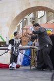 Cerveza-Sheva, ISRAEL - 5 de marzo de 2015: Muchacho judío en un traje negro y pila negra en etapa con el mago - Purim Imagen de archivo