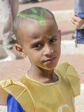 Cerveza-Sheva, ISRAEL - 5 de marzo de 2015: Retrato de un niño negro en un vestido amarillo con un modelo en el pelo - Purim Fotografía de archivo libre de regalías