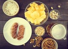 Cerveza y bocados fijados: microprocesadores, pistacho, pretzel, salchicha, nueces Fotografía de archivo
