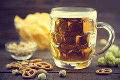 Cerveza y bocados fijados: microprocesadores, pistacho, pretzel, y nueces en bla Imagen de archivo