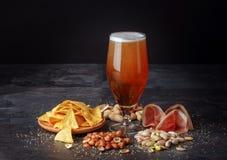Cerveza y bocados salados en una tabla negra Bebida alcohólica con las nueces y los microprocesadores Concepto de la celebración  Fotografía de archivo libre de regalías