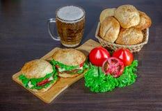 Cerveza y bollos hechos en casa de las hamburguesas con las empanadas de carne de vaca y los ingredientes frescos de la ensalada Foto de archivo