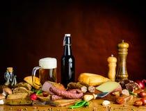 Cerveza y comida en la tabla de madera Imagenes de archivo