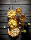 Cerveza y diversas clases de bocados en los cuencos en la tabla de cortar foto de archivo libre de regalías