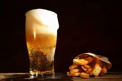 Cerveza y patatas fritas Fotos de archivo libres de regalías