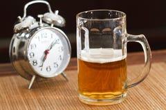 Cerveza y reloj de alarma Fotos de archivo