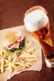 Cerveza y una hamburguesa Fotografía de archivo libre de regalías