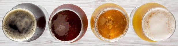 Cervezas clasificadas en una superficie de madera blanca, visi?n superior De arriba, desde arriba imagen de archivo libre de regalías