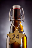 24 cervezas de Navidad en la estrella alrededor de la botella Imágenes de archivo libres de regalías