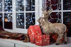 Cervi decorativi che stanno su un davanzale vicino ai contenitori di regalo rossi Immagine Stock Libera da Diritti