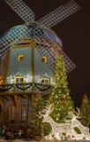 Cervi fatti dalla ghirlanda sotto l'albero di Natale ed il mulino a vento Fotografia Stock