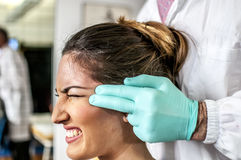 Cervical and headache. Medical doctor visits a young girl suffering cervical and headache Royalty Free Stock Images