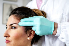 Cervical and headache. Medical doctor visits a young girl suffering cervical and headache Stock Image